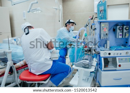 Surgeons save the life of the patient perform surgery in intensive care monitoring vital signs