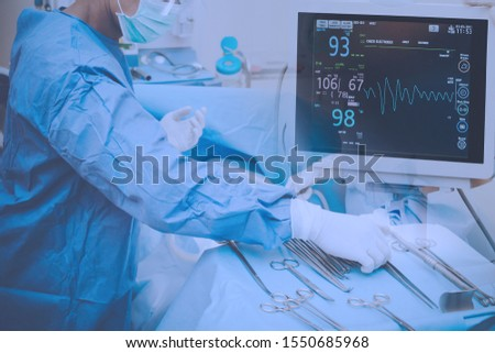 Surgeons team holding medical instruments performing surgery with patient sleeping on operation bed in operation room at hospital. Medical and Healthcare concept.