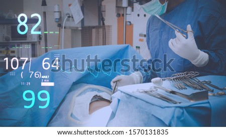 Surgeons team holding medical instruments performing surgery with patient sleeping on operation bed in operation room at hospital. Medical and Healthcare concept. #1570131835