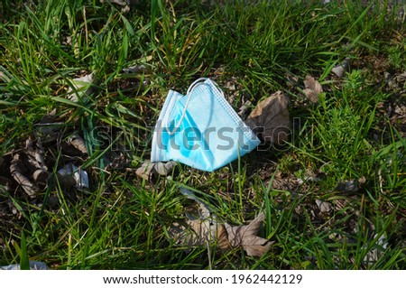 Surgical face mask abandoned in the wild, thrown away in the grass amid the Coronavirus pandemic ; illustration for waste pollution of the environment Photo stock ©