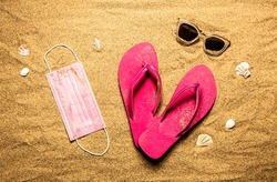 Surgical face mask, pink flip flops and sunglasses on the sand. Summer vacation (holiday) while coronavirus (Covid-19) epidemic concept. Beach from above (top view, flat lay).
