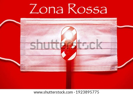 Surgical mask with a traffic light with a red light with the text 'Zona Rossa' translating in italian 'Red zone' concept of red zone during Corona Virus Foto stock ©