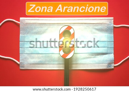 Surgical mask with a traffic light with a yellow light, and text 'zona Arancione' translating in orange zone, concept of orange zone during Corona Virus Foto stock ©