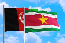 Suriname and Afghanistan national flag waving in the wind on a deep blue sky together. High quality fabric. International relations concept.