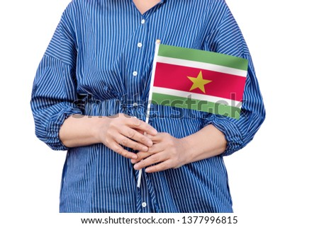 Suriname flag. Close up of woman's hands holding a national flag of Suriname isolated on white background. #1377996815