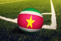 Suriname flag on ball at corner kick position, soccer field background. National football theme on green grass.