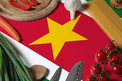 Suriname flag on fresh vegetables and knife concept wooden table. Cooking concept with preparing background theme.