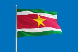 Suriname national flag waving in the wind on a deep blue sky. High quality fabric. International relations concept.