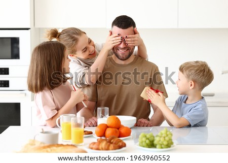 Surpise for daddy. Cute smiling children siblings giving father wrapped gift box and postcard. Young mom congratulating husband with kids while having breakfast in kitchen. Family holiday concept