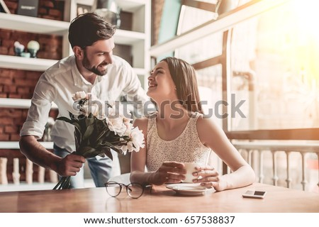 Surprise! Beautiful romantic couple in cafe. Young man is presenting flowers to his beloved. Feel of happiness.