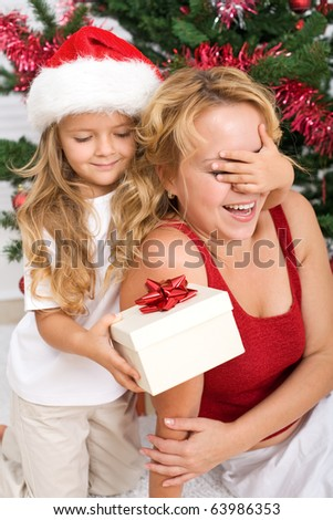 Surprise christmas present - little girl and woman in front of the decorated tree