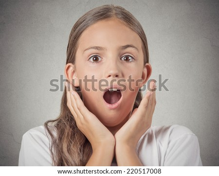 Surprise. Closeup portrait headshot teenager girl shocked with wide open mouth eyes, jaw drop, blown away isolated grey wall background. Human emotion facial expression feeling body language reaction