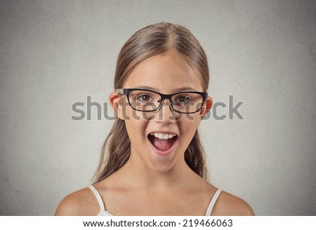 Surprise. Closeup portrait teenager girl with glasses shocked wide open mouth eyes jaw drop blown away isolated grey wall background. Human emotion facial expression feeling body language reaction