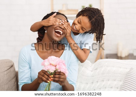 Surprise Concept. Laughing african woman holding flowers, little girl covering her eyes, copyspace