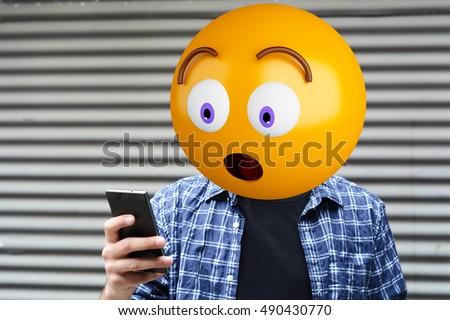 Surprise emoji head man using a smartphone. Emoji concept