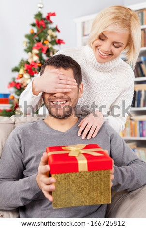 Surprise! Handsome young man sitting on the couch and holding a gift box while her girlfriend standing behind him and covering his eyes with hands