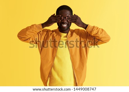 Surprise. Happy black man closing eyes with hands on yellow background. Portrait of smiling african american male model waiting for surprising gift, studio shot #1449008747