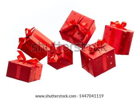 Surprise in flying boxes wrapped in red gift paper with bow on white background. Concept of holidays and greeting cards. Copy space.