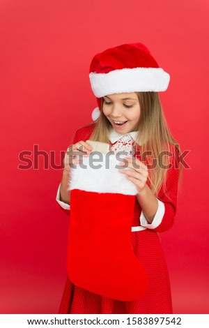 Surprise inside. Surprised child hold stocking. Little girl open stocking stuffed with present. Red stocking for xmas gift. Boxing day. Christmas stocking or sock. Saint Nicholas Day or Christmas Eve.