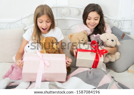 Surprise inside. Surprised children in morning. Little girls open present boxes in bed. Gift surprise. Receiving birthday surprise. Celebrate big day with surprise. Happy holidays.
