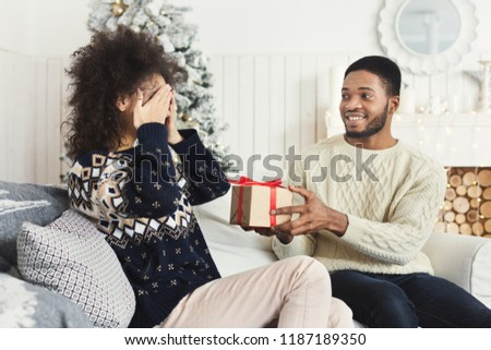 Surprise on Christmas. Happy man surprising his girlfriend with xmas gift, excited woman closing her eyes, copy space #1187189350