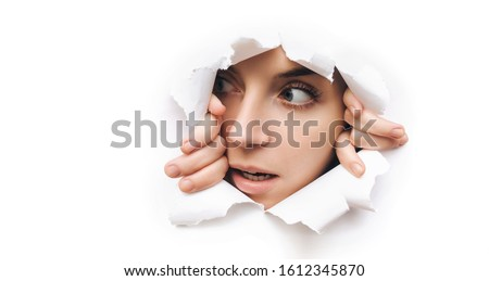 Surprise. Portrait of a young caucasian woman looking through the hole in white paper. Distrustful look. Women's curiosity and gossip. A jealous wife. Copy space. Сток-фото ©