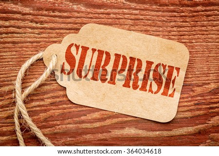 surprise red stencil text on a paper price tag against rustic wood #364034618