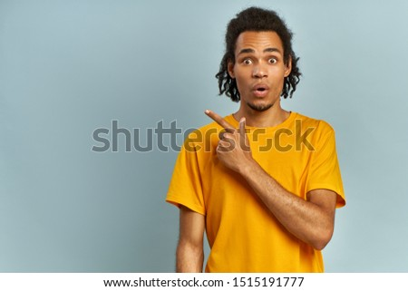 Surprised African American male hipster, keeps the mouth open, being stupefied as advertises something, wears fashionable orange t-short, indicates with fore finger at upper right corner. Omg concept
