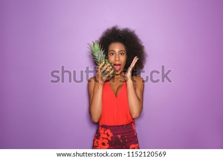 Surprised African-American woman with pineapple on color background #1152120569