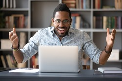 Surprised African guy sitting at desk looking at computer screen makes big eyes feels shocked by unbelievable news, got opportunity new job, low price discounts sale, lottery or betting win concept