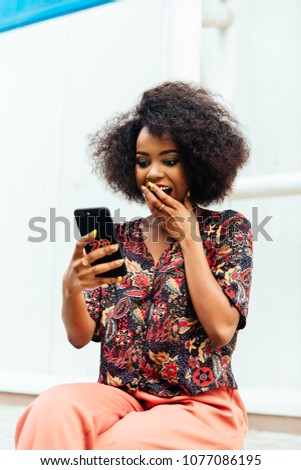 Surprised african woman, covering her mouth by hand while looking at smartphone screen. Dressed in colorful clothes. Resting outdoors.