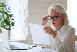 Surprised aged woman worker in glasses sit at office desk reading paper document or contract feel confused with bad news, frustrated senior businesswoman stunned by received paperwork correspondence