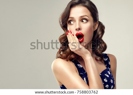 Surprised and amazed girl holds  her cheeks and looks aside .  Beautiful woman with curly hair and red nails. Expressive facial expressions.