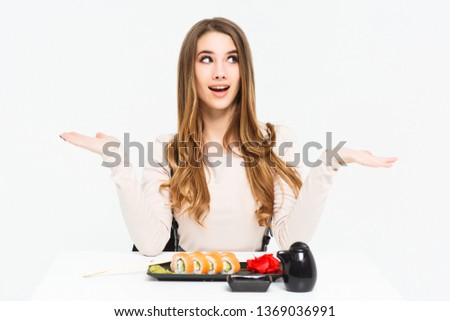 Surprised and candid woman sitting with sushi nigiri isolated on white! #1369036991