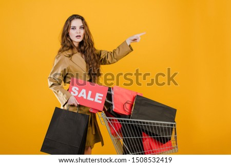 surprised and excited girl has sale sign and pushcart with colorful shopping bags and signal tape isolated over yellow