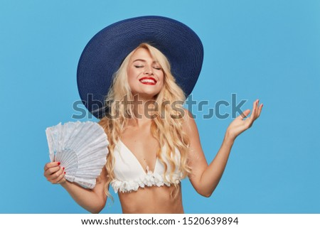 Surprised and pleasure young woman in a swimsuit, hat  and  fan on a blue background. Unexpected good news. Travel and vacation discounts. Healthy people