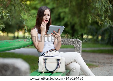 Surprised and worried young woman getting bad news on tablet computer / huge smartphone
