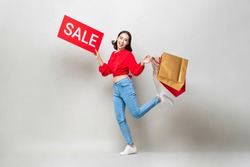 Surprised Asian woman holding shopping bags and red sale sign isolated in gray studio background for Chinese new year sale concept