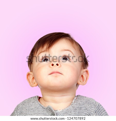 Surprised baby girl looking up isolated on pink background