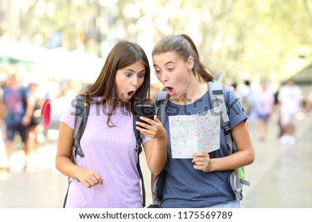 Surprised backpackers finding travel information in a smart phone in the street