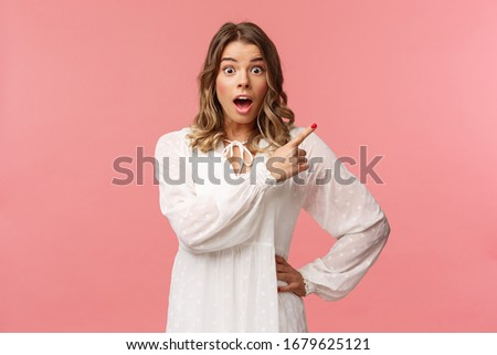 Surprised beautiful blond girl pointing upper right corner, gasping amused and staring at camera with fascinated expression, open mouth in awe to ask question about promo, pink background Foto stock ©