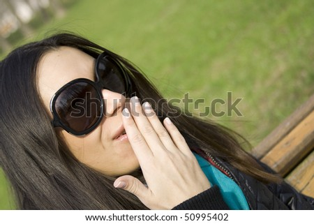 Surprised beautiful woman in the park laughs and covers his mouth with his hand