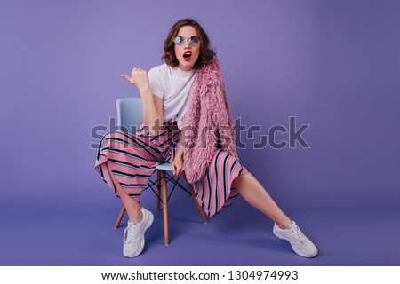 Surprised beautiful woman with wavy hairstyle sitting on chair. Studio photo of funny white lady in sneakers expressing amazement on purple background.