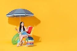 Surprised beautiful young Asian woman sitting on beach chair doing an open palm gesture isolated on bright yellow studio background with copy space