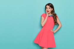 Surprised beautiful young woman in pink mini dress posing with hand on chin and looking at camera. Three quarter length studio shot on turquoise background.