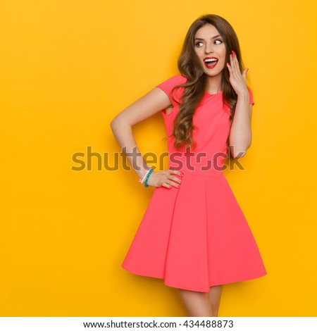 Surprised beautiful young woman with curly long brown hair standing with hand on hip and shouting. Three quarter length studio shot on yellow background.