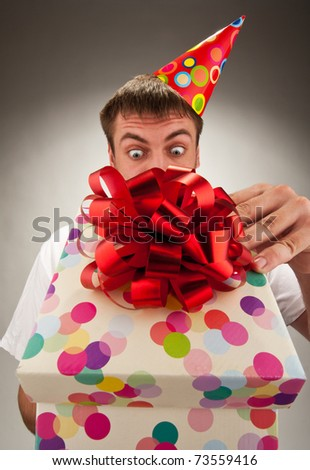 Surprised birthday man opening big gift box