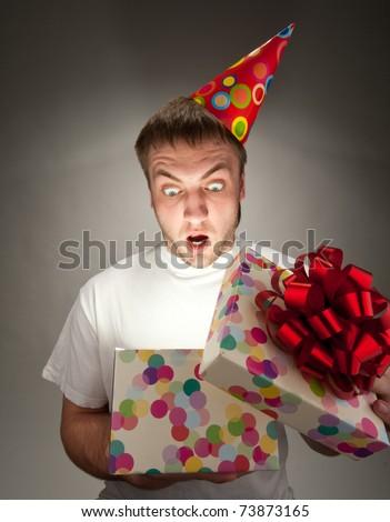 Surprised birthday man opening big gift box