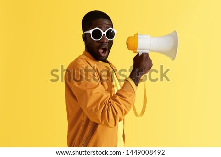 Surprised black man with megaphone on yellow background. Studio portrait of shocked african american male model in fashion sunglasses with loud speaker Photo stock ©