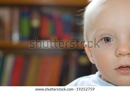 Surprised boy indoor bookshelf